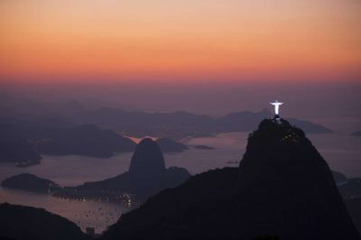 This photo shows the Christ the Redeemer statue, located on the top of Corcovado Mountain and the Sugar Loaf Mountain, are seen from the Parque Nacional da Tijuca, or Tijuca national park in Rio de Janeiro, Brazil.