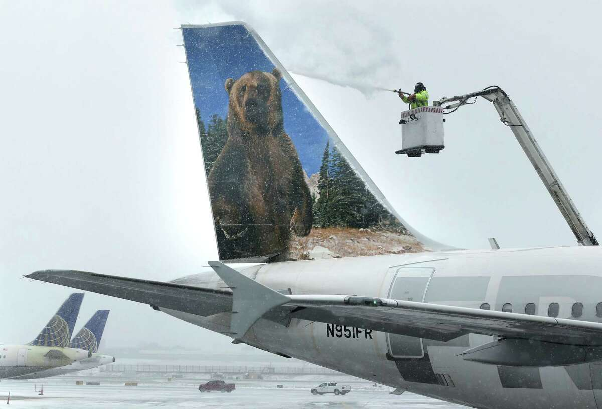 A crewmember de-ices a Frontier Airlines plane at LaGuardia Airport in New York, Monday, Jan. 26, 2015. More than 5,000 flights in and out of East Coast airports have been canceled as a major snowstorm packing up to three feet of snow barrels down on the region.