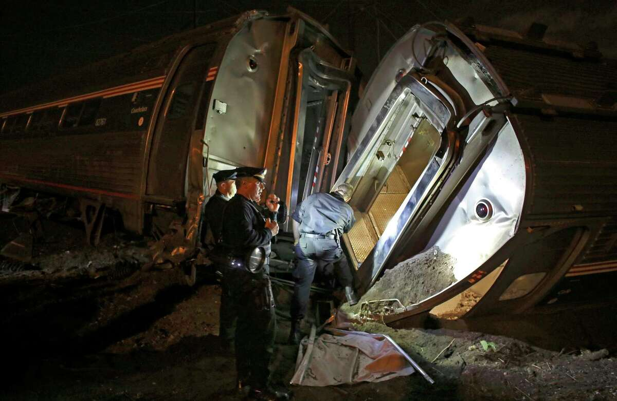 In this May 12, 2015 photo, emergency personnel work the scene of a train wreck An Amtrak train headed to New York City derailed and crashed in Philadelphia. Amtrak says it will install video cameras inside locomotive cabs that record the actions of train engineers.