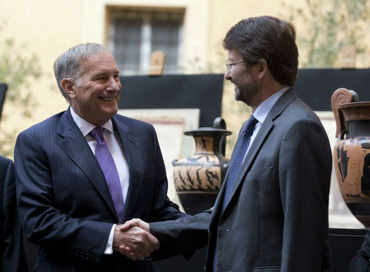 US Ambassador to Italy John Phillip, left, and Italian Culture Minister Dario Franceschini shake hands for photographers at the end of press conference to present ancient artifacts returned to Italy by The United States, in Rome, Tuesday.