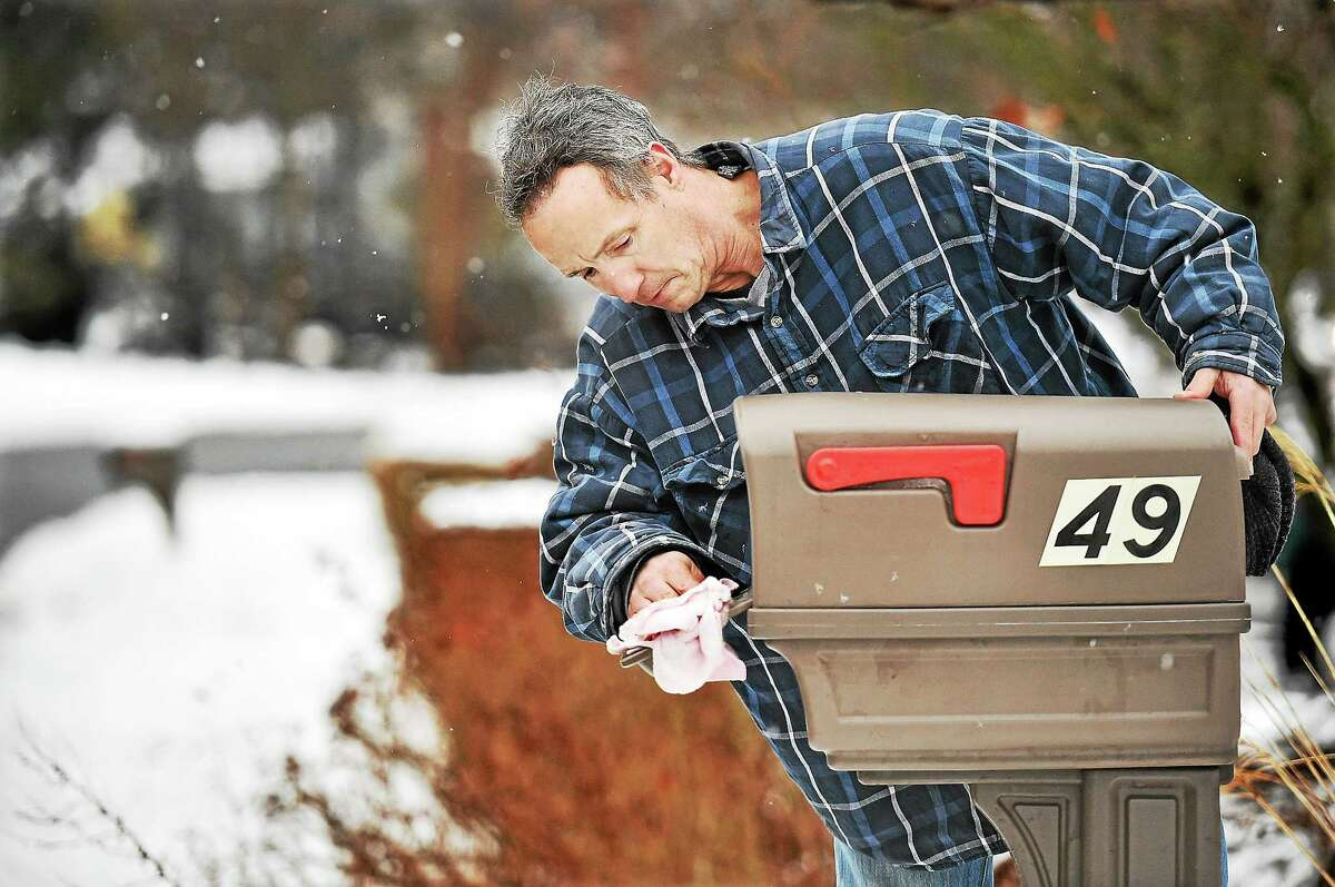 """North Haven resident Russell Bell wipes down his Rubbermaid mailbox as snow begins to fall again on Saturday afternoon, January 24, 2015. Bell said, """"It's a chronic problem, the snow plow comes along and the weight of this heavy snow pushed the box right off. Thank goodness the pole is in tact and the box just slides back together again."""""""