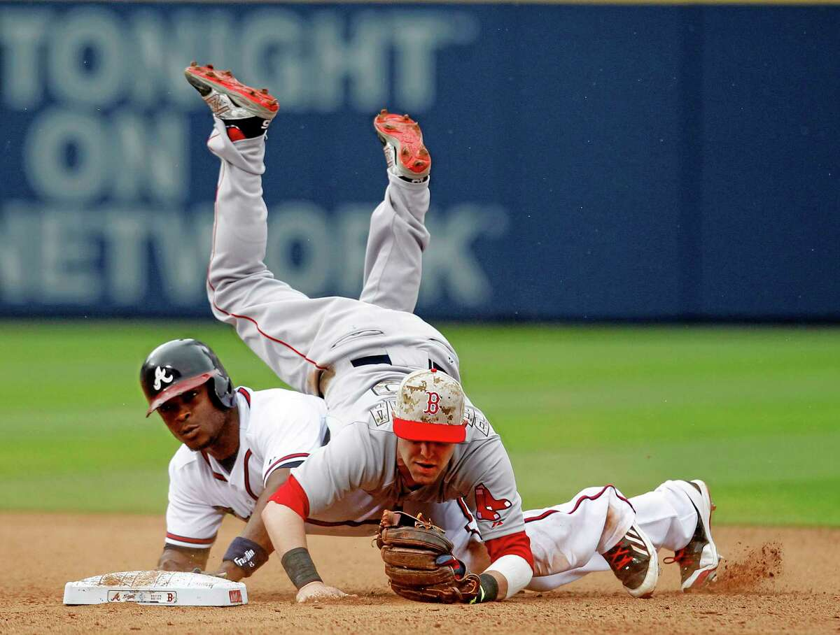 Boston Red Sox second baseman Dustin Pedroia (15) flips over the Braves' Justin Upton after he throws to first base for the double play during the sixth inning of Monday's game in Atlanta.