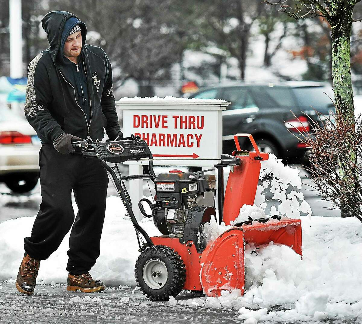 Kiel Loricco, employed by Paradise Landscaping in New Haven uses an Airens snow blower to clear the sidewalks at the CVS on the corner of Lakeslee and Washington avenue in North Haven on Saturday, January 24, 2015. Loricco said the job will take about two hours to do the CVS and the complex next door.