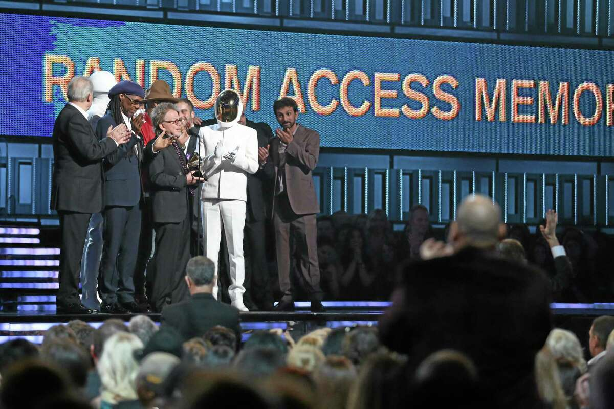 """Paul Williams, center, accepts the award for album of the year for Daft Punk's """"Random Access Memories"""" at the 56th annual Grammy Awards at Staples Center on Sunday, Jan. 26, 2014, in Los Angeles. (Photo by Matt Sayles/Invision/AP)"""