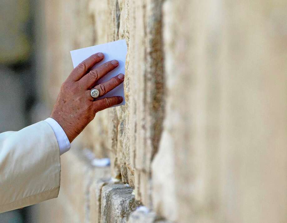 Pope Francis places an envelope Monday in one of the cracks between the stones of the Western Wall, the holiest place where Jews can pray, in the old city of Jerusalem, Israel. Photo: AP Photo/Andrew Medichini  / AP
