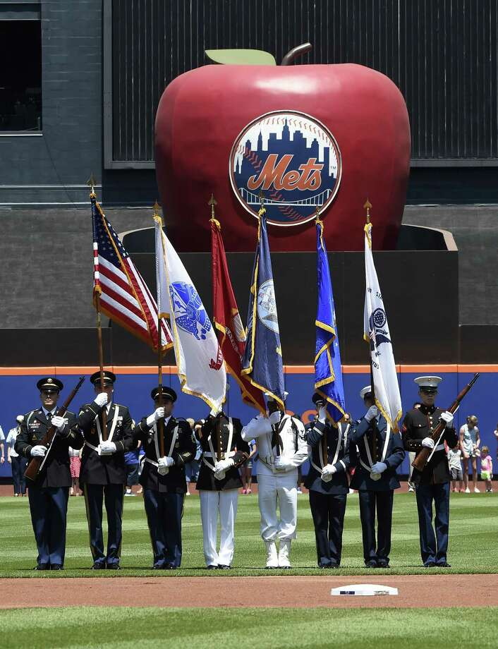 The United States Joint Service color guard present the colors before Monday's game between the Mets and Philadelphia Phillies in New York. Photo: Kathy Kmonicek — The Associated Press  / FR170189 AP
