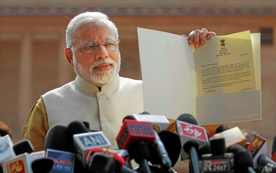 File - In this Tuesday, May 20, 2014 file photo, India's Prime Minister-elect Narendra Modi displays the letter from the Indian president inviting him to form the new government, outside the Presidential Palace in New Delhi, India. A spokesman for Modi says he plans to invite the leader of rival Pakistan to his inauguration along with other South Asian leaders. (AP Photo/Altaf Qadri, File) Photo: AP / AP