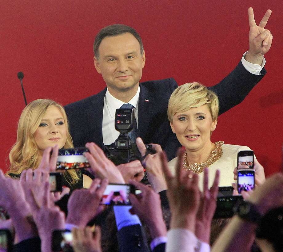 Opposition candidate Andrzej Duda, center, with wife Agata, right, and daughter Kinga greet supporters as first exit polls in the presidential runoff voting are announced, in Warsaw, Poland, Sunday, May 24, 2015. Polish President Bronislaw Komorowski conceded defeat in the presidential election Sunday after an exit poll showed him trailing Duda, a previously little-known right-wing politician.(AP Photo/Czarek Sokolowski) Photo: AP / AP