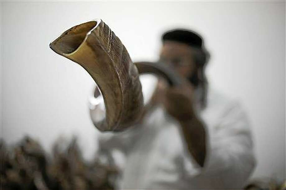 In this photo from Monday, Moshe Manos tests a shofar, or ram's horn, before purchasing one at a workshop that produces them in Tel Aviv, Israel. A shofar is traditionally used during the Jewish New Year holiday of Rosh Hashana which starts at sundown on Wednesday. Photo: (AP Photo/Ariel Schalit) / AP