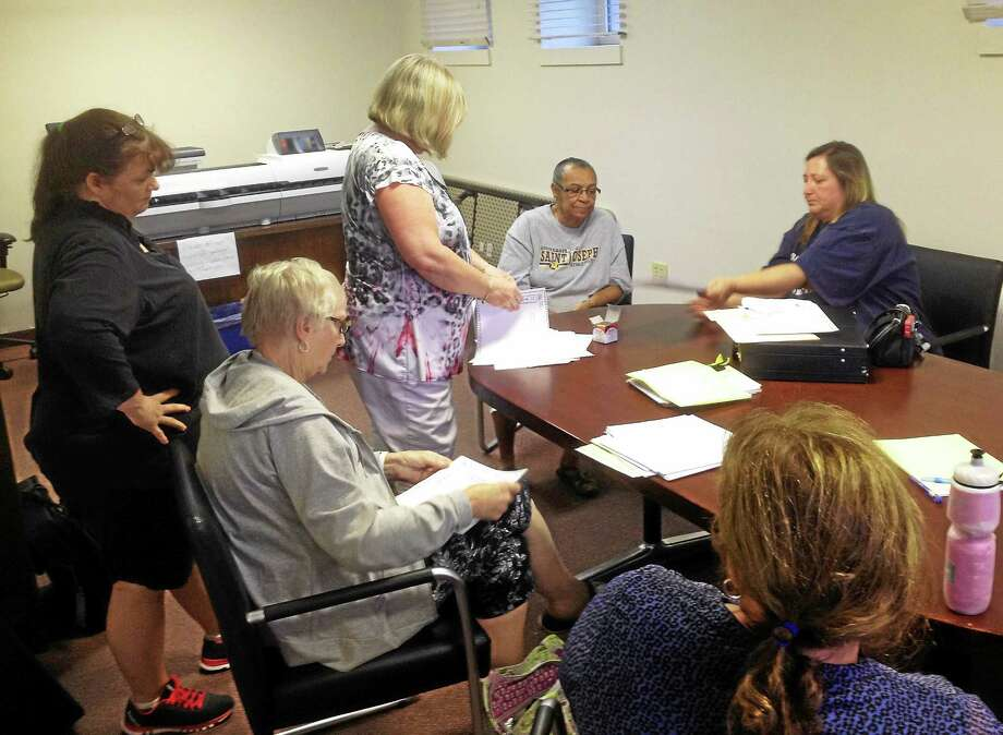 From left, official checker Sandra Chiasson, Registrar of Voters Athena Neville; moderator Kelly Mainetti (center); tabulator Odessa Buttram; and official checker Ramona Quinn conduct a recount Tuesday of last week's Portland Democratic primary. Photo: Jeff Mill — The Middletown Press