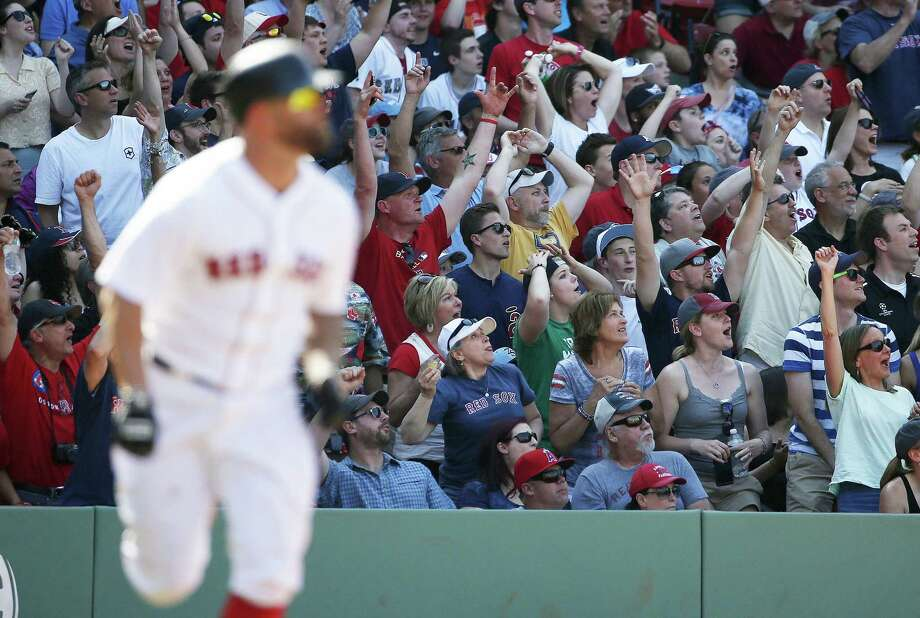 Fans cheer as Mike Napoli, left, watches his two-run double during the eighth inning Sunday. Photo: Michael Dwyer — The Associated Press  / AP