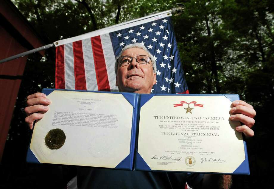 U.S. Army veteran Bill Dwyer of Southbury holds the documentation of  the U.S. military's Bronze Star awarded to his brother, Tom Dwyer of the U.S. Air Force's 56th Special Operations Wing in Thailand,  was killed on May 13, 1975, as a part of the assault force to ordered to recapture the USS Mayaguez and rescue its crew from Cambodian forces in what is known as the last official battle of the Vietnam War. Photo: (Peter Hvizdak - New Haven Register)  / ©Peter Hvizdak /  New Haven Register