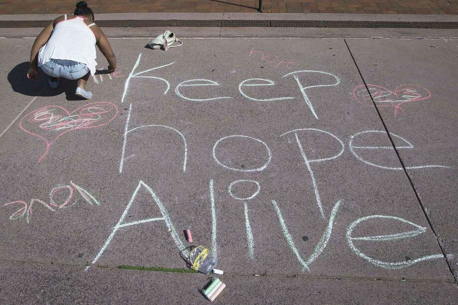 A protestor writes a message on the sidewalk outside the Cuyahoga County Justice Center on May 23, 2015, in Cleveland. Michael Brelo, a patrolman charged in the shooting deaths of two unarmed suspects during a 137-shot barrage of gunfire was acquitted Saturday in a case that helped prompt the U.S. Department of Justice to determine the city police department had a history of using excessive force and violating civil rights. Photo: AP Photo/John Minchillo  / AP