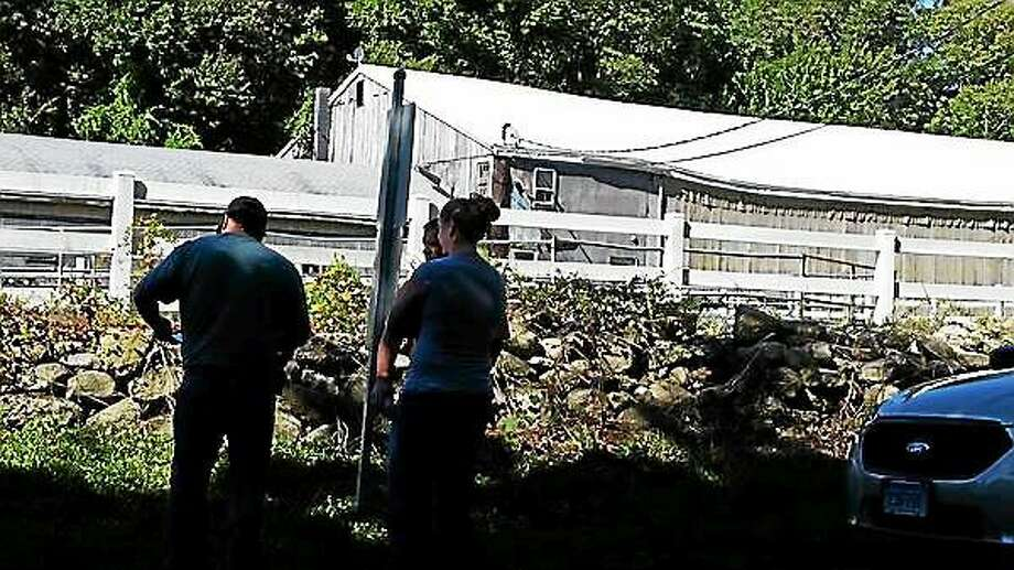 State police are still investigating an assault that took place last week on White Birch Road in East Hampton. Here, owners who board their equines at White Birch Farm wait to feed their horses. Photo: Kathleen Schassler - The Middletown Press