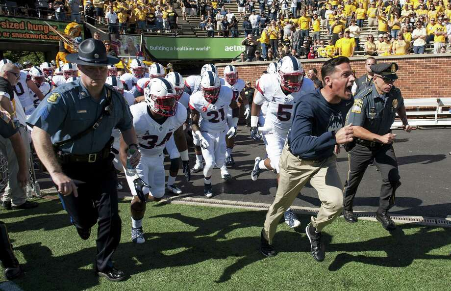 UConn coach Bob Diaco, right, leads his team onto the field before the start of the Huskies' game against Missouri on Saturday in Columbia, Mo. Photo: L.G. Patterson — The Associated Press  / FR23535 AP