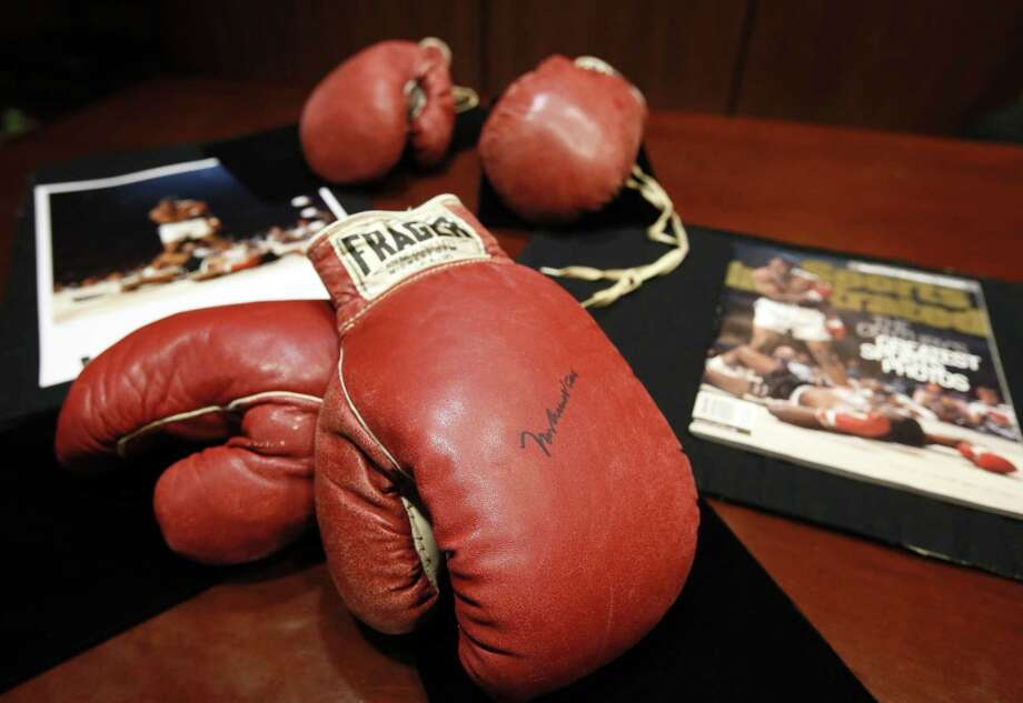 The boxing gloves of Muhammad Ali, front, and of Sonny Liston, rear, sit on a table at Heritage Auctions by a photo and magazine depicting a moment captured during the fight, Thursday, Jan. 22, 2015, in Dallas. The 1965 rematch between Ali and Liston remains one of the most controversial sporting events of the 20th century. To this day, 50 years later, questions swirl. Was it a knockout or ìphantom punchî that Ali threw when he decked Liston minutes into the first round of their heavyweight title fight. (AP Photo/Tony Gutierrez) Photo: AP / AP