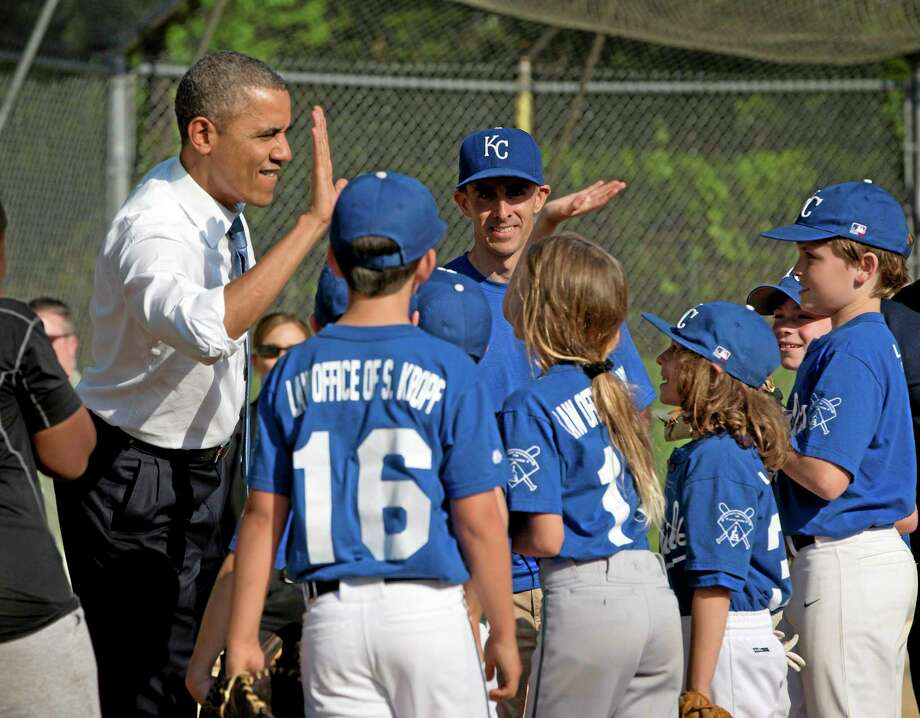 In this May 19, 2014, photo, President Barack Obama greets players as he makes an unannounced stop to surprise members of the Northwest little league baseball teams at Friendship Park in Washington.  Obama seems to have caught a bad case of cabin fever. Since taking office, Obama has periodically grumbled about the claustrophobia that sets in when his every move is surrounded by intense security, rendering it nearly impossible to enjoy the simple pleasures that private citizens take for granted. But in recent days, the president has made more of a point to get out.  (AP Photo/Pablo Martinez Monsivais) Photo: AP / AP