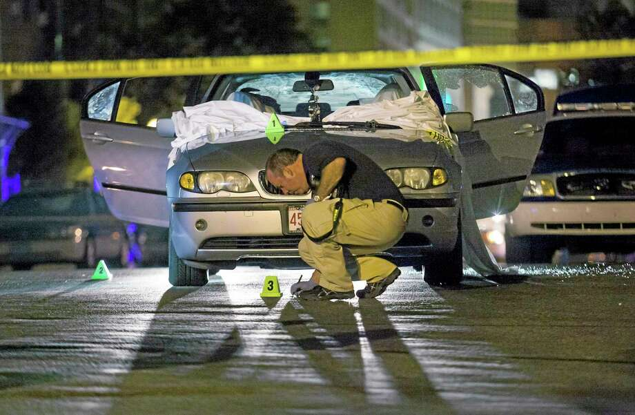 In this July 16, 2012, file photo, Boston Police investigate a car in which Daniel de Abreu and Safiro Furtado were shot to death near the intersection of Herald Street and Shawmut Avenue in Boston. In May of 2014 prosecutors announced that former New England Patriots star Aaron Hernandez had been indicted on murder charges in their deaths. Hernandez is awaiting trial in the separate 2013 shooting death of Odin Lloyd, whose body was found in North Attleborough, Mass., not far from Hernandez's home. Photo: (AP Photo/Courtney Sacco) / AP