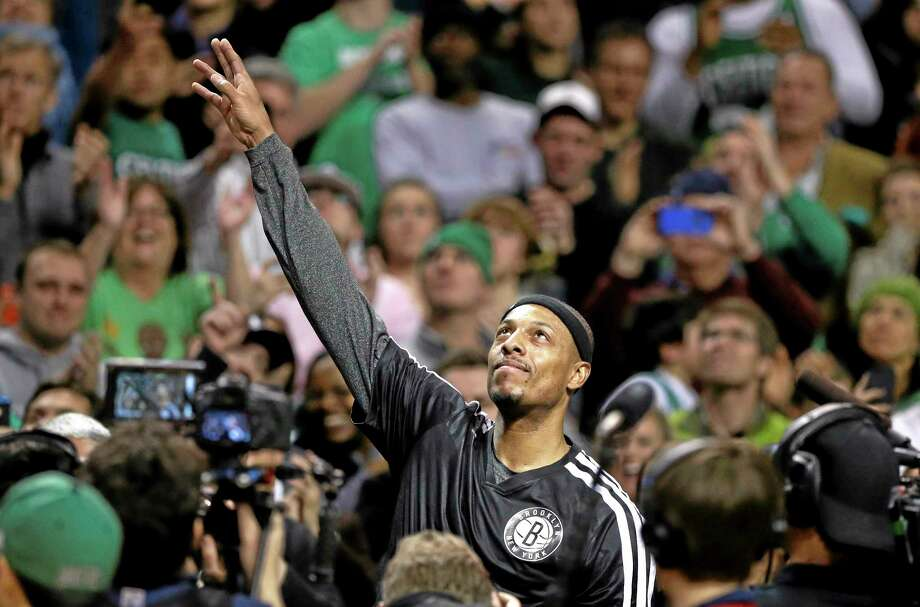 Brooklyn Nets forward Paul Pierce, center, formerly of the Boston Celtics, waves to the crowd during a tribute to him in an NBA basketball game against the Boston Celtics, Sunday, Jan. 26, 2014, in Boston. (AP Photo/Steven Senne) Photo: AP / AP