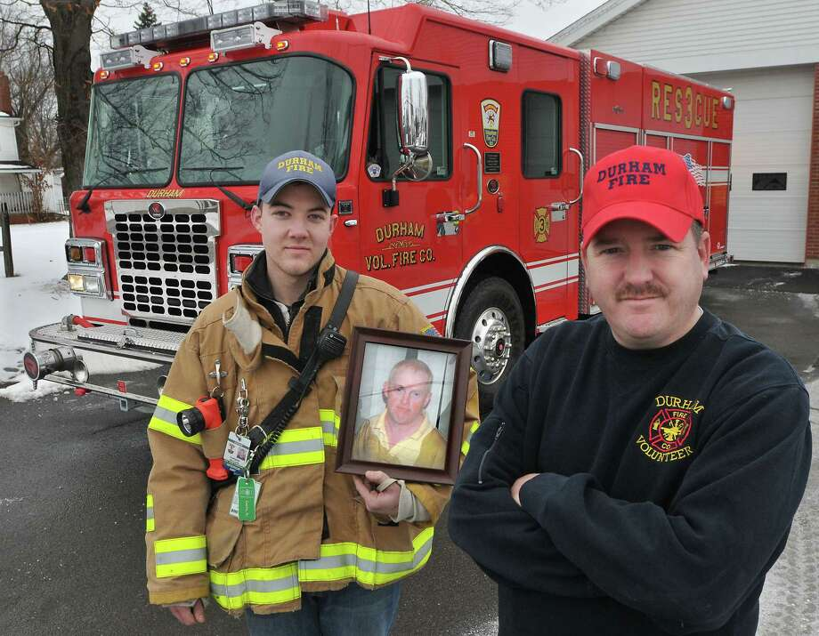 Chief Rob Chadd, at right and Captain Bill Curtis, with the Durham Volunteer Fire Company's newest truck, Rescue 3. Curtis holds a picture of Durham resident, Charlie Larsen, an honorary member of the company, passed away at the age of 52 on Feb. 6, 2013. Rescue 3 was dedicated in Larsen's memory in November 2013 at the company's annual banquet. Photo: Catherine Avalone — The Middletown Press  / TheMiddletownPress