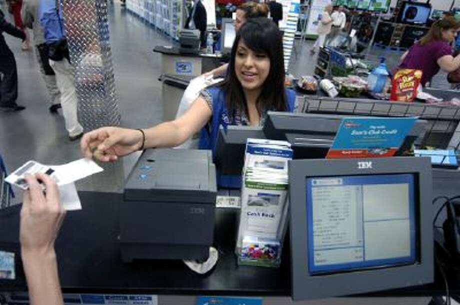 Sam's Club Inc. cashier Jessica Cornejo hands a receipt to a customer in Bentonville, Ark., on Thursday, June 4, 2009.