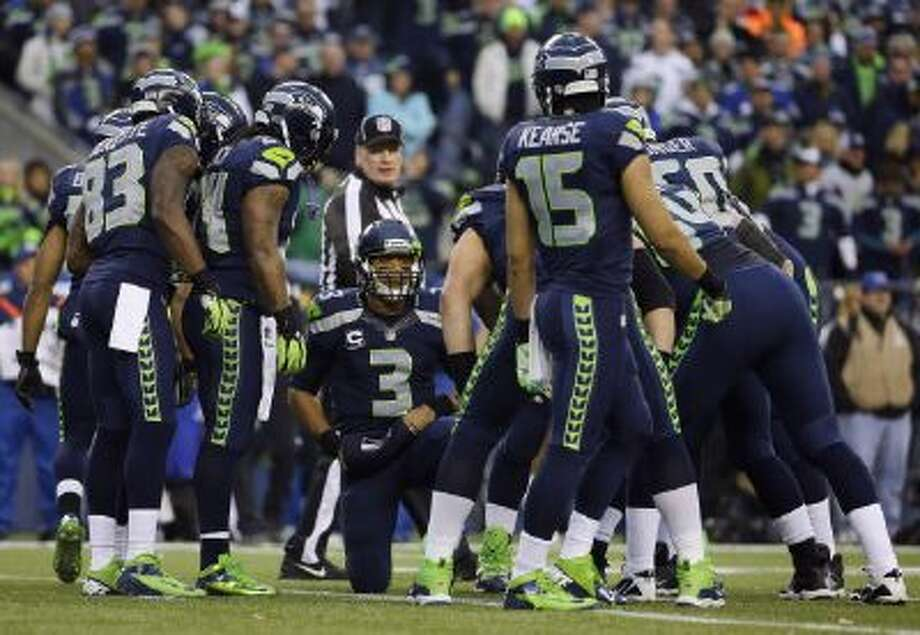 Seattle Seahawks QB Russell Wilson (3) speaks to his teammates, including receivers Ricardo Lockette (83) and Jermaine Kearse (15), during a huddle in the first half of the NFC championship against the San Francisco 49ers in Seattle.