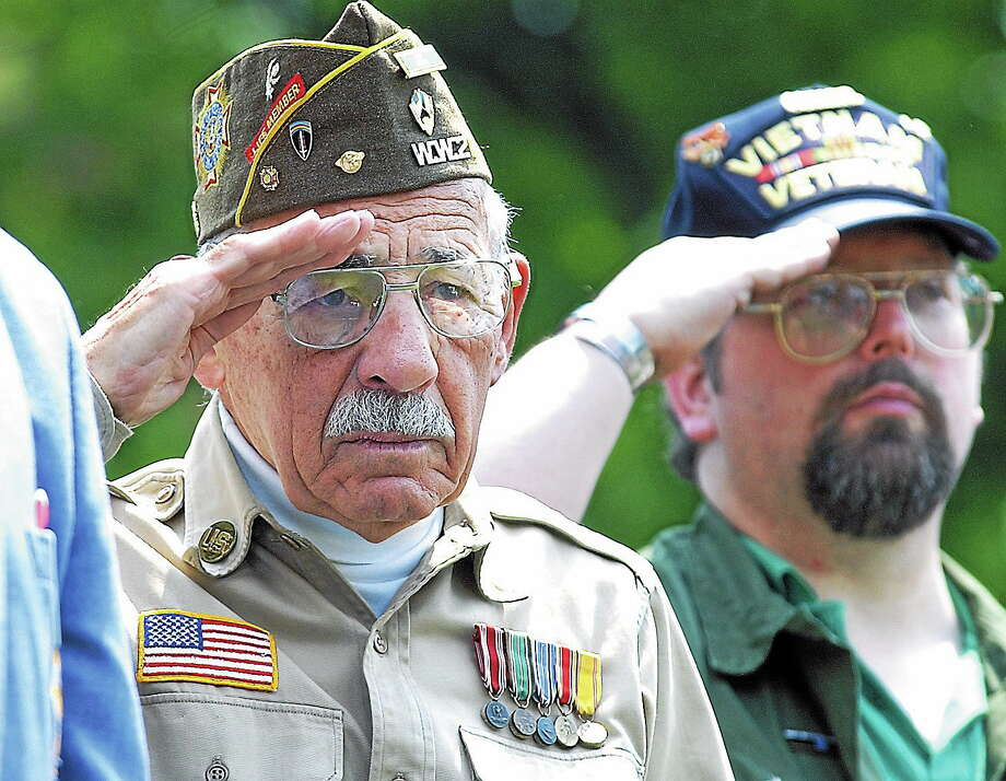 May 27, 2002 - James Tobits, V.F.W. 583 and parade organizer and Vietnam vet Martin Reardon salute the American flag during the national anthem at Union Park in Middletown on Monday. (Tom Warren/The Middletown Press) Photo: Journal Register Co.
