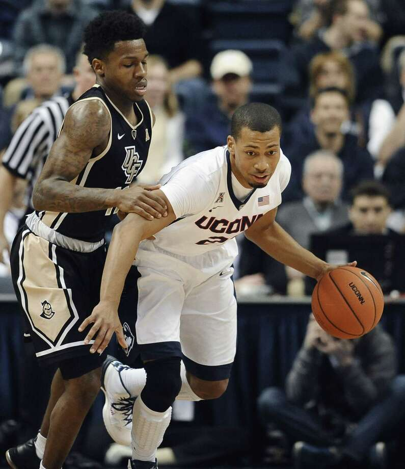 UConn's Omar Calhoun, right, dribbles past UCF's Brandon Goodwin during the first half Thursday. Photo: Jessica Hill — The Associated Press  / FR125654 AP