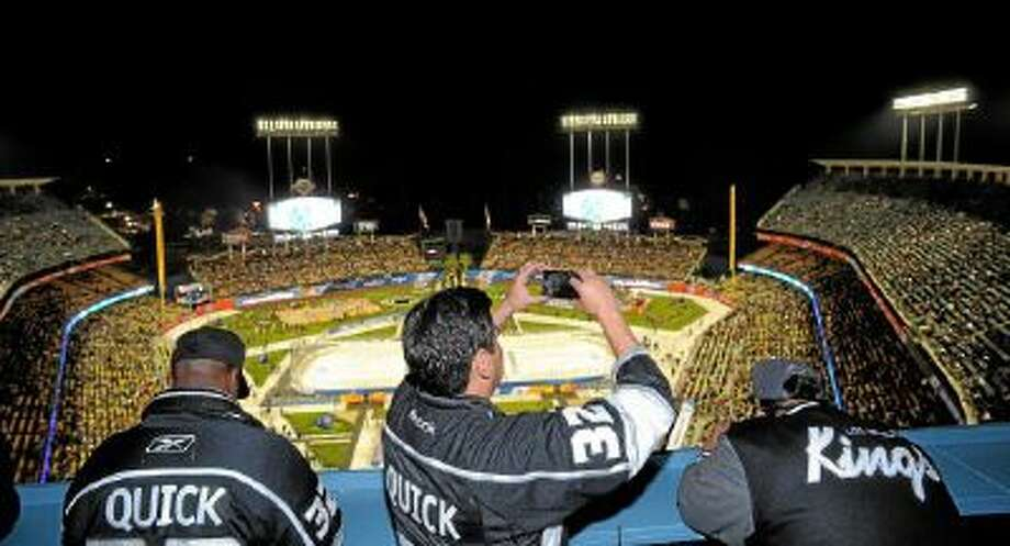 Fans watch the 2014 NHL Stadium Series featuring the Los Angeles Kings taking on the Anaheim Ducks at Dodger Stadium Saturday.