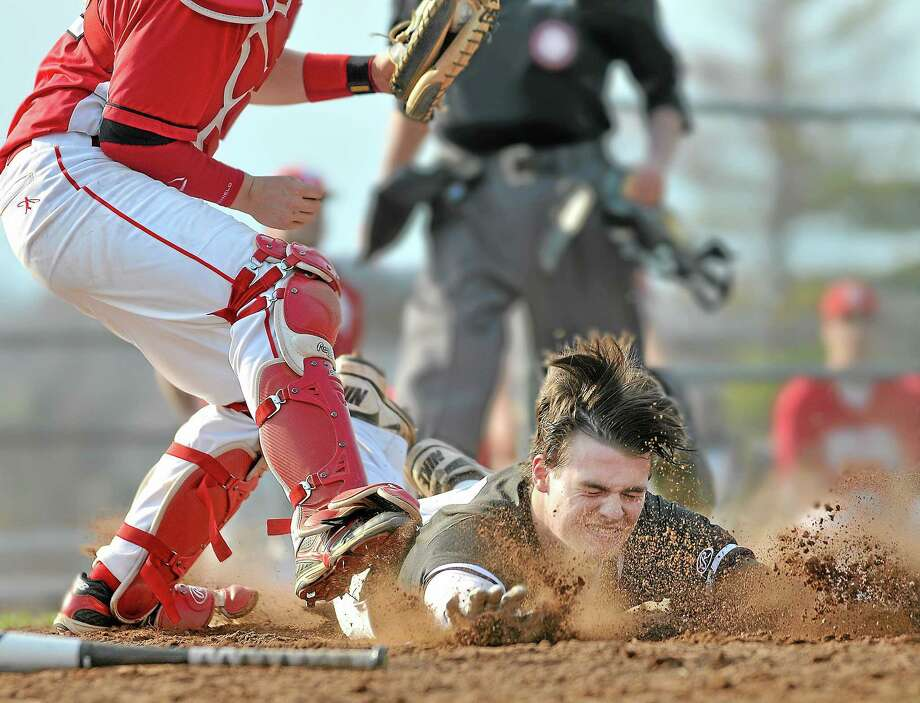 Xavier sophomore right fielder Pat Downey slides in safe as Fairfield Prep catcher Jake Berry is late with the tag in a game where the Falcons defeated the Fairfield Prep Jesuits 7-1 at home in 2013. This photo won second place at the annual SPJ awards. Photo: Catherine Avalone — The Middletown Press   / TheMiddletownPress