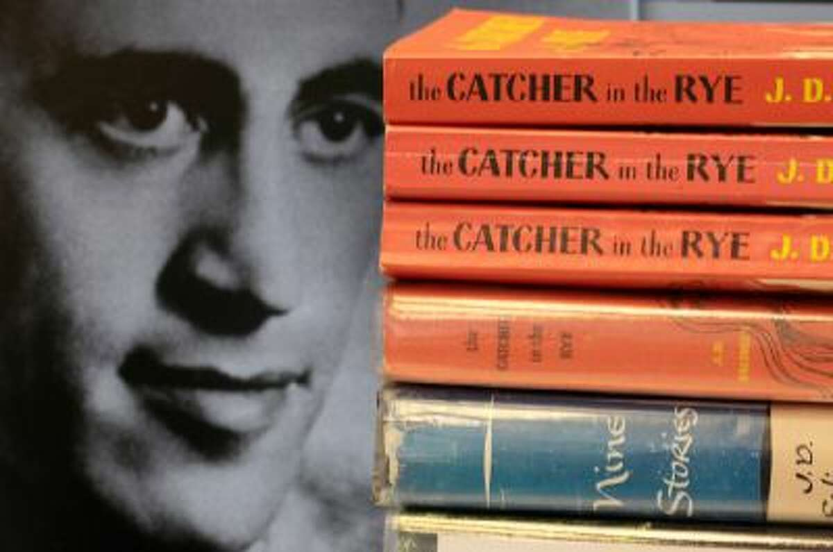 """A photo of J.D. Salinger appears next to copies of his classic novel """"The Catcher in the Rye"""" as well as his volume of short stories called """"Nine Stories"""" at the Orange Public Library in Orange Village, Ohio."""