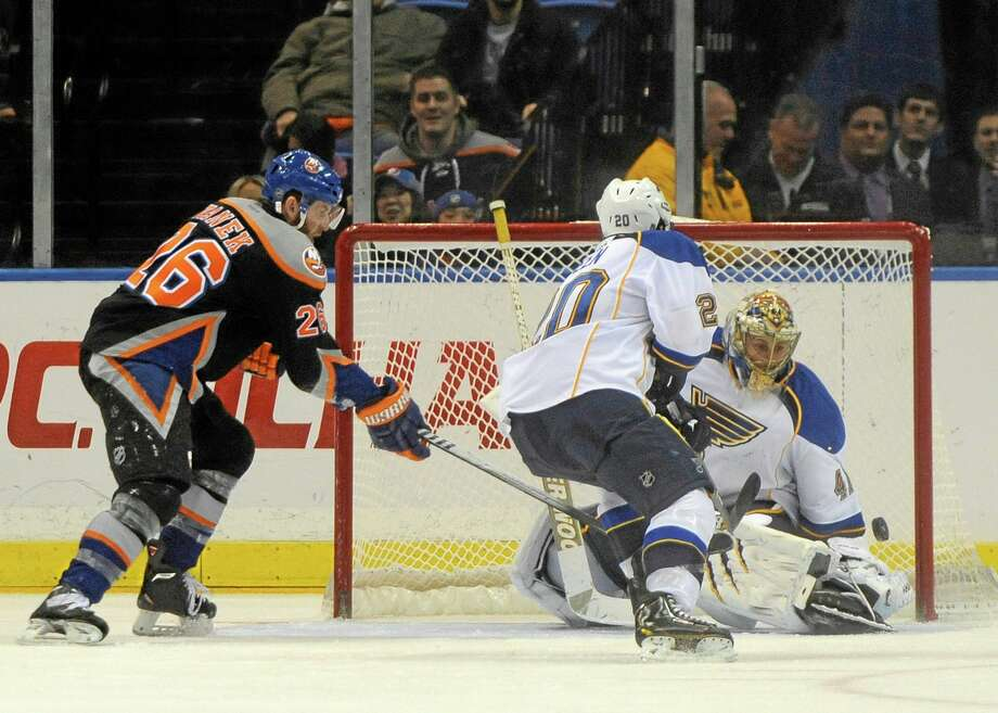 The Islanders' Thomas Vanek (26) shoots the puck past St. Louis Blues goalie Jaroslav Halak as Alexander Steen watches during overtime on Saturday in Uniondale, N.Y. The goal did not count as the referees declared Vanek kicked the puck into the goal with his skate. The Blues beat New York 4-3 in a shootout. Photo: Kathy Kmonicek — The Associated Press  / FR170189 AP