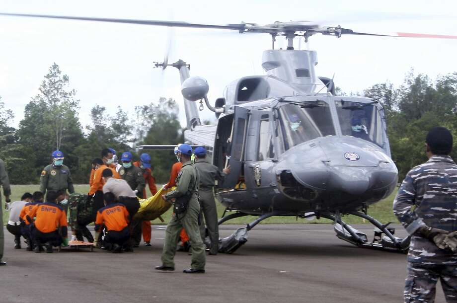Indonesian military personnel unload the bodies believed to be the victims of AirAsia Flight 8501 from a helicopter at Iskandar Airport in Pangkalan Bun, Central Borneo, Indonesia, on Jan. 22, 2015. (AP Photo) Photo: AP / AP