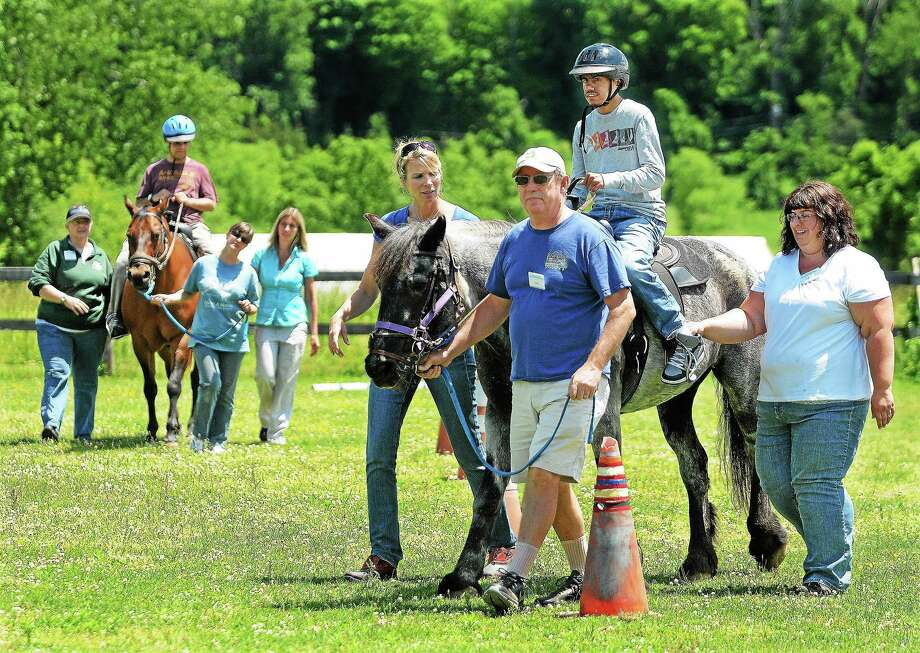 Kevin Ajodhi, a student at Wethersfield Transitional Academy learns first time riding skills and verbal communications at Manes & Motions Therapeutic Riding Center on Millbrook Road in Middletown. Photo: Catherine Avalone -- The Middletown Press  / TheMiddletownPress