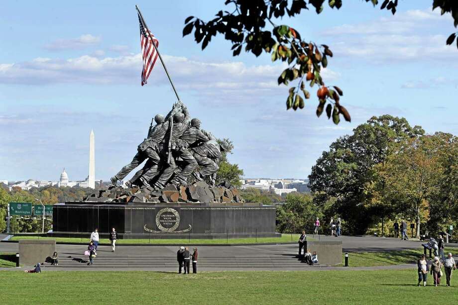 In this archive photo, people enjoy pleasantly warm fall temperatures as the leaves start to turn colors at the Iwo Jima Memorial, also known as the U. S. Marine Corps War Memorial, in Arlington, Va., with a view of Washington in the background. Photo: File Photo  / AP