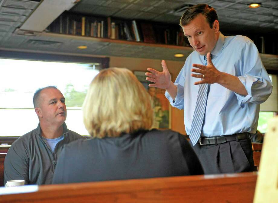 U.S. Sen. Chris Murphy, right, talks with Chris Sudock, left, and Laura Sudock, center, at a diner in Meriden in this 2012 file photo from when he was running for office. Photo: AP File Photo  / FR125654 AP