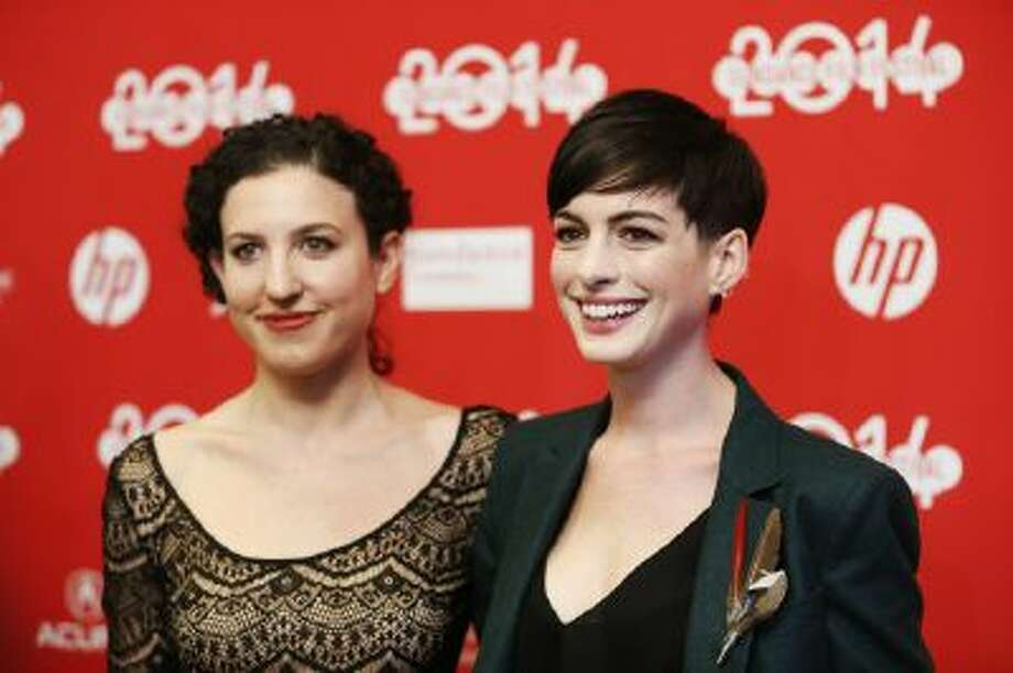 """In this Mon., Jan. 20, 2014 file photo, writer and director Kate Barker-Froyland, left, and cast member Anne Hathaway, pose together at the premiere of the film """"Song One"""" during the 2014 Sundance Film Festival, in Park City, Utah."""