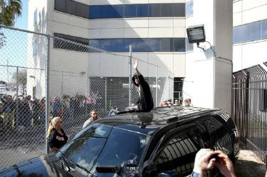 Justin Bieber waves after exiting from the Turner Guilford Knight Correctional Center on January 23, 2014 in Miami, Florida. Justin Bieber was charged with drunken driving, resisting arrest and driving without a valid license after Miami Beach police found the pop star street racing Thursday morning.