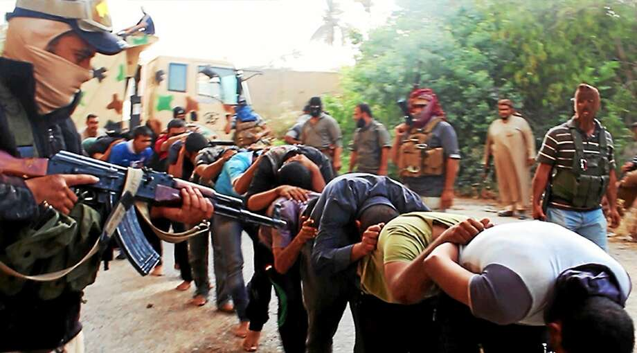 This June 14, 2014 file image posted on a militant website which has been verified and is consistent with other AP reporting, appears to show militants from the Islamic State group leading away captured Iraqi soldiers dressed in plain clothes after taking over a base in Tikrit, Iraq. The Islamic State group is richer than al-Qaida, operates a modern, effective media arm and holds much more territory than al-Qaida ever did. Photo: AP Photo Via Militant Website, File  / AP2012