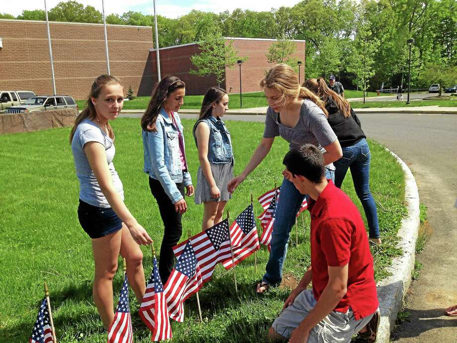 Jeff Mill - The Middletown Press Portland High School students plant flags on school grounds to honor 65 veterans who were killed in Iraq or Afghanistan. Photo: Journal Register Co.