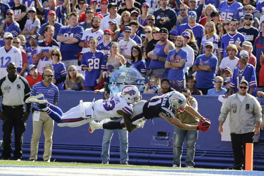 Bills free safety Aaron Williams (23) tackles Patriots wide receiver Julian Edelman in the end zone during the second half Sunday. Photo: Bill Wippert — The Associated Press  / FR170745 AP