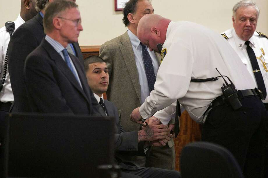 A court officer places handcuffs on the wrists of former New England Patriots football player Aaron Hernandez after the guilty verdict was read during his murder trial at the Bristol County Superior Court in Fall River, Mass., Wednesday, April 15, 2015.  Hernandez was found guilty of first-degree murder in the shooting death of Odin Lloyd in June 2013.  He faces a mandatory sentence of life in prison without parole.  (Dominick Reuter/Pool Photo via AP) Photo: AP / Pool Reuters