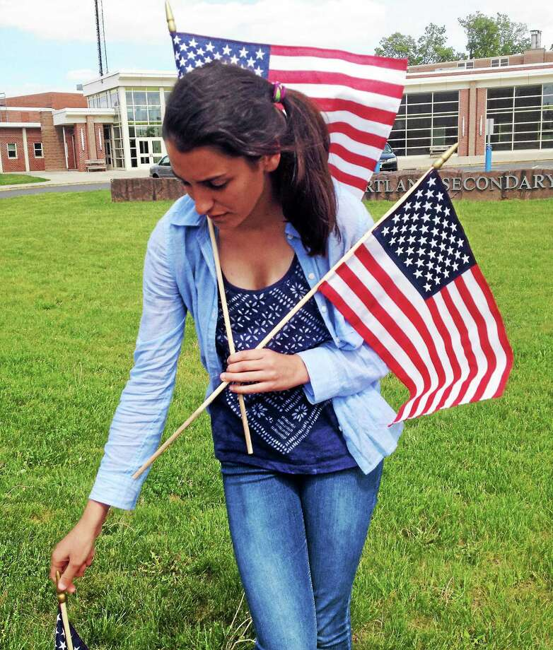 Portland Middle School Student Council members carefully positioned 65 flags on the lawn in honor of the Connecticut servicemen and women who sacrified their lives during the Afghanistan and Iraq wars. Photo: Jeff Mill — The Middletown Press