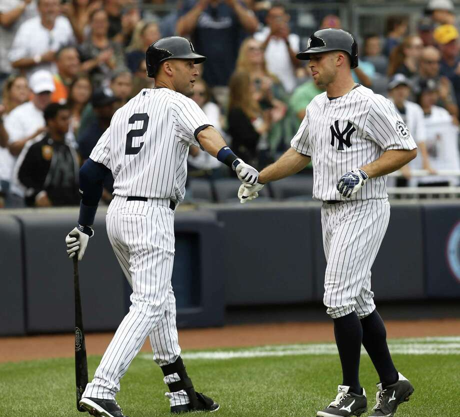Brett Gardner, right, is greeted by Derek Jeter after he hit a solo home run during the fifth inning Sunday. Photo: Seth Wenig — The Associated Press  / AP