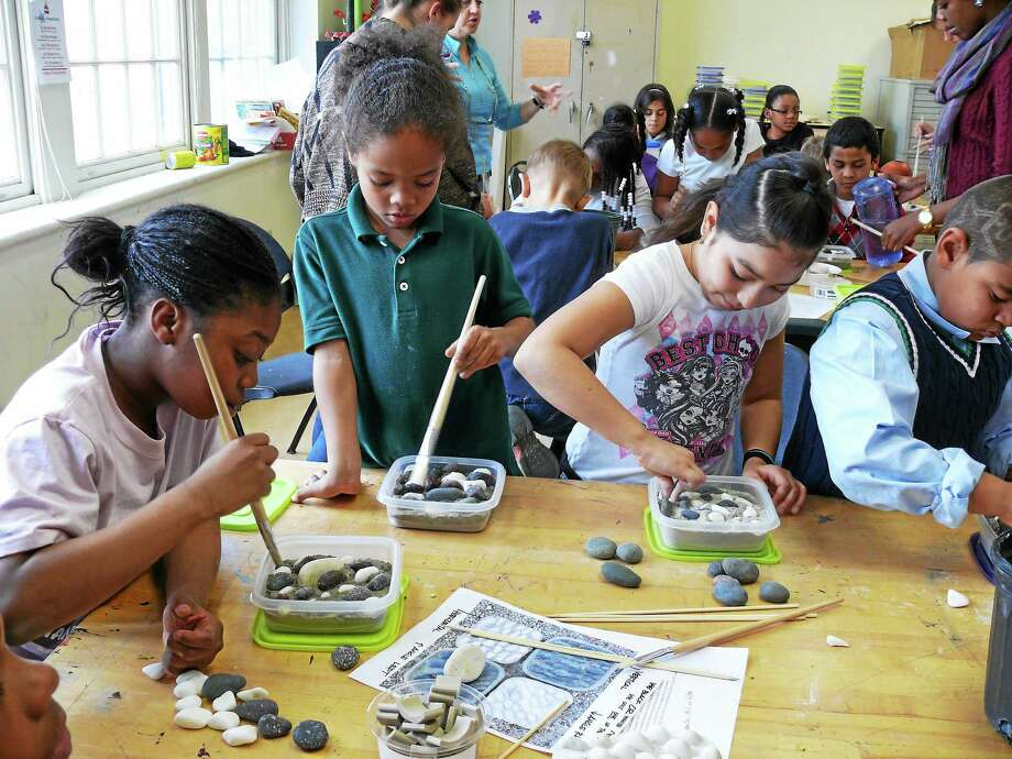 Children work during Green Street Art Center's after-school program making pebble mosaics last year for the entry way. Photo: Submitted Photo