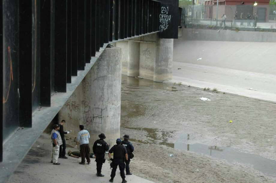 FILE - In this June 7, 2010 file photo, Mexican federal police and forensic experts stand next to the body of Sergio Adrian Hernandez Huereca, 15, under the Paso Del Norte border bridge, as U.S. officials watch from the U.S. side at right, in Ciudad Juarez, northern Mexico. On Wednesday, Jan 21, 2015, a federal appeals court in New Orleans revisits the question of whether the Mexican teenagerís rights were violated under the U.S. Constitution when he was killed in his home country by a bullet allegedly fired by a federal agent from across the border in Texas.(AP Photo) Photo: AP / AP