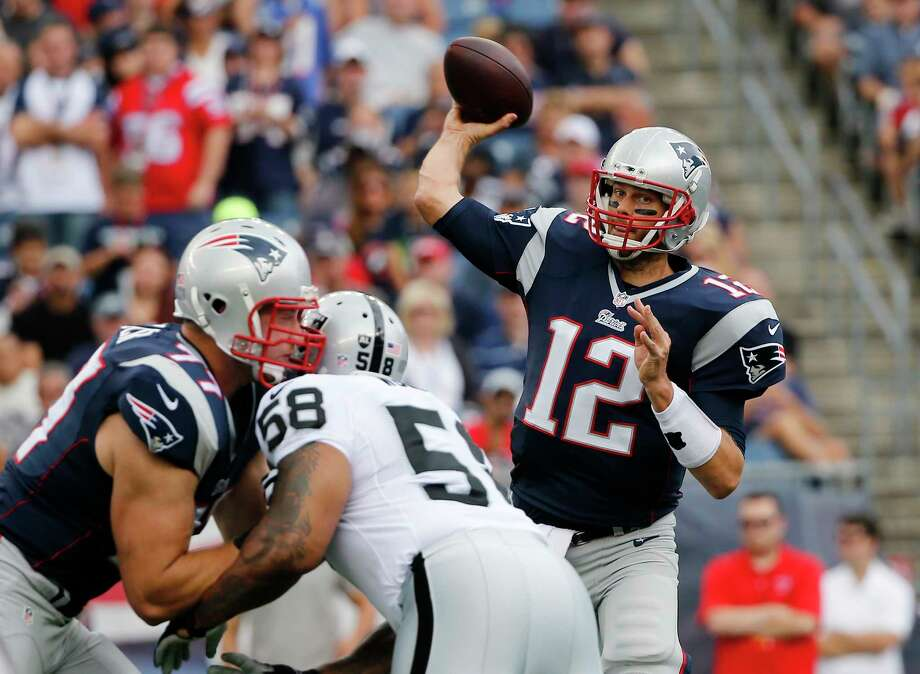 Patriots quarterback Tom Brady looks for a receiver over Raiders defensive end LaMarr Woodley in the first half Sunday. Photo: Elise Amendola — The Associated Press  / AP