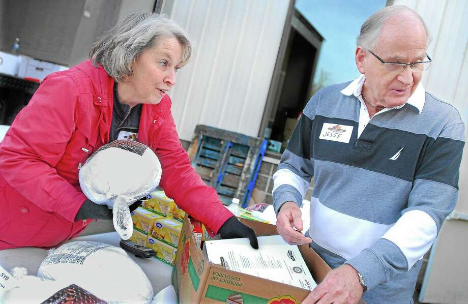Volunteers from Fellowship Church and the Middletown Interfaith Community distribute Thanksgiving baskets prepared by the members of the Middletown Community Thanksgiving Project in this file photo. Photo: File Photo