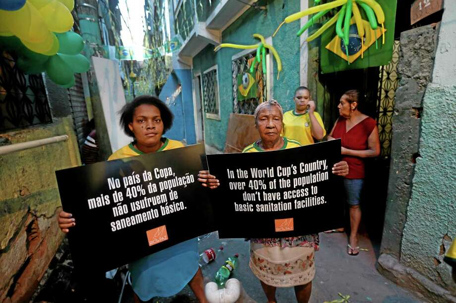 """Women hold signs that read in Portuguese: """"In World Cup country, more than 40 percent of the population don't have access to basic sanitation facilities"""" as they participate in a protest outside their homes in the Jacarezinho slum in Rio de Janeiro, Brazil, Wednesday, May 21, 2014. Organized by Rio de Paz, protesters say the public money spent on the international soccer tournament should have been used to improve schools, health care and security in shantytowns. (AP Photo/Silvia Izquierdo) Photo: AP / AP"""