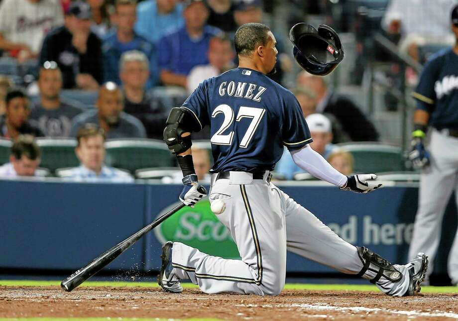Milwaukee Brewers center fielder Carlos Gomez loses his helmet as he swings and misses during a game against the Braves on Monday in Atlanta. Photo: John Bazemore — The Associated Press  / AP
